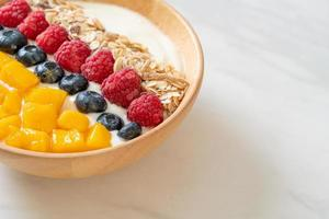 zelfgemaakte yoghurtkom met framboos, bosbes, mango en granola - gezonde voedingsstijl foto