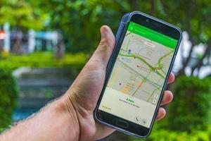 taxi-app voor het grijpen van auto's op het telefoonscherm in bangkok, thailand foto