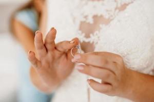 de bruid raakt zachtjes haar geliefde verlovingsring aan foto