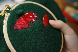 meisjeshandborduurwerk paddestoelhoed in hoepel. foto