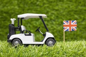 golfkar met Union Jack-vlag is op groene grasachtergrond foto