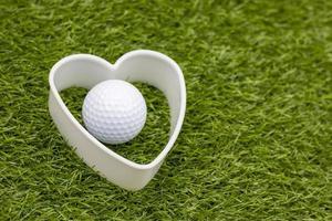 golfbal met wit hart ligt op groen gras foto