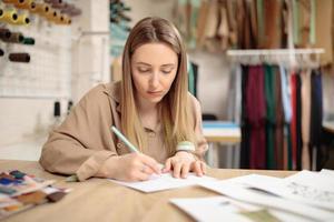 jonge vrouwelijke modeontwerper tekening schets met model zittend in haar kantoor. foto