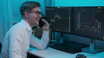 thuishandelaar met telefoon en handelsgrafieken op de aandelenmarkt op het computerscherm thuis. man in brillen aan de telefoon met praten aan de telefoon foto