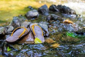 pantoffels werden op de rots in het water gelegd foto