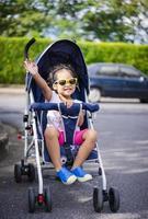 klein meisje glimlachend in kinderwagenstoel op parkeerplaats foto