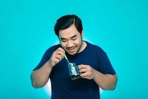 de jonge man roerde een kopje koffie met een grote glimlach. blauwe achtergrond foto