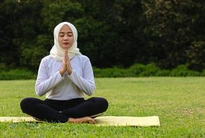 jonge Aziatische moslimvrouw zittend op het gras, genietend van meditatie foto