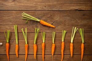 verse baby wortelen op houten snijplank en houten achtergrond foto