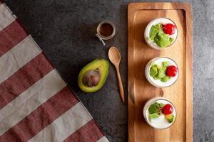 glas kers en avocado gesneden in yoghurt op houten achtergrond foto