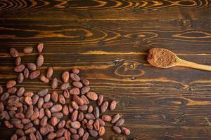 cacaobonen en cacaopoeder in houten lepel op oude natuurlijke houten achtergrond foto