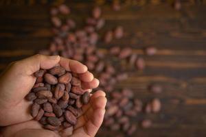 cacaobonen in de hand op oude natuurlijke houten achtergrond foto