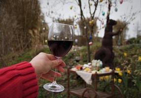 glas rode wijn in de vrouwelijke hand en paasboom met decoratie en feestelijke ontbijtbrunch op de retro mobiele tafel in de tuin. foto