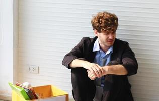 zakenman ontslagen van baan, zittend, depressief en gestrest door ontslagen. foto