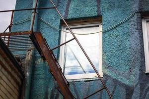 wit raam in blauwe getextureerde muur met roestige metalen trap eronder foto