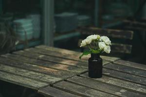 mooie bloemen in een bruine glazen fles die 's ochtends op een houten tafel in de tuin wordt geplaatst foto