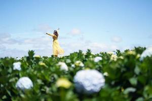 gelukkige aziatische vrouw houdt haar hand vast in een veld met hortensiabloemen foto