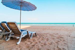 lege strandstoel op zand met oceaanzeeachtergrond foto