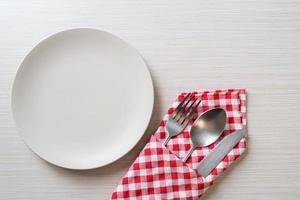 lege plaat of schotel met mes, vork en lepel op houten tegelachtergrond foto