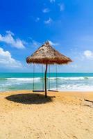 schommel op het strand met oceaanzee en blauwe hemelachtergrond foto