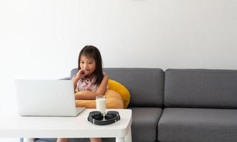 een jong Aziatisch meisje dat computer gebruikt om thuis te leren als protocol voor sociale afstand tijdens covid-19 of coronaviruspandemie. thuisonderwijs concept foto