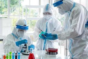 wetenschappers in persoonlijke beschermingsmiddelen of pbm die onderzoek doen en experimenteren om medicijnen te vinden voor de behandeling van covid-19 of coronavirusinfectie in het laboratorium foto