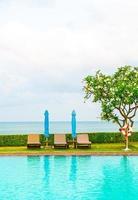 stoel zwembad en parasol rond zwembad met oceaan zee achtergrond foto