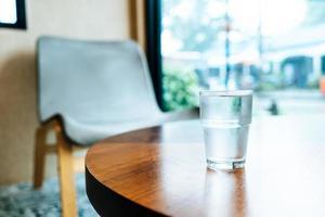 glas water op houten tafel foto