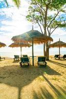 parasols en strandstoelen met kokospalmen en zee strand achtergrond en blauwe lucht - vakantie en vakantie concept foto