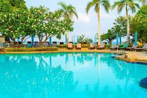 stoelzwembaden en parasols rond zwembad met kokospalmen - vakanties en vakantieconcept foto