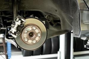 schijfauto close-up - monteur die auto-onderdelen losschroeft terwijl hij onder een opgeheven auto werkt foto