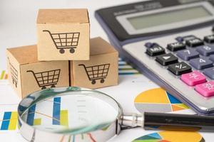 winkelwagen logo op doos met vergrootglas op grafiek achtergrond. bankrekening, investeringsanalytische onderzoeksgegevenseconomie, handel, zakelijk import export transport online bedrijfsconcept. foto