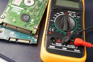 multimeter met moederbord, onderhoud, reparatie en controle van computerhardwareconcept. foto