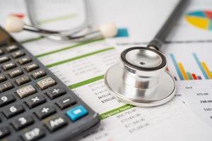 stethoscoop op rekenmachine, financiën, account, statistieken, analytische onderzoeksgegevens en bedrijfsconcept voor medische gezondheid. foto