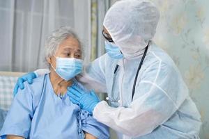 aziatische arts met gezichtsschild en pbm-pak nieuw normaal om te controleren of de patiënt de veiligheidsinfectie beschermt covid-19 coronavirus-uitbraak op de quarantaine verpleegafdeling. foto