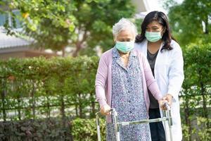 arts helpt aziatische senior of oudere oude dame vrouw lopen met rollator en het dragen van een gezichtsmasker ter bescherming van de veiligheidsinfectie en het doden van het nieuwe coronavirus covid-19 virus. foto