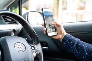 bangkok, thailand, 1 juli 2020 met iphone in toyota sienta-auto om te communiceren met familie en vrienden. foto