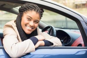 gelukkige Afro-Amerikaanse vrouw in een auto rijden, herfst-winter foto