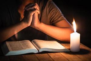 religieuze concepten, de jonge man bad op de bijbel in de kamer en stak de kaarsen aan om te verlichten. foto