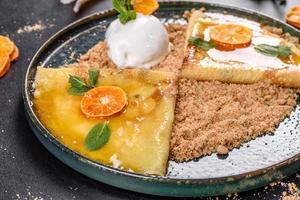 heerlijke verse pannenkoeken op een bord met zoete saus en ijs versierd met munt foto