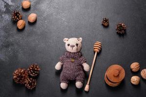 speelgoedbeer gebonden van wollen draden op een donkere achtergrond foto