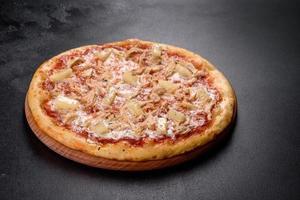 smakelijke verse ovenpizza met tomaten, kaas en ananas op een donkere betonnen ondergrond foto