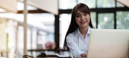portret van een mooie jonge vrouw die studeert terwijl ze aan tafel zit foto