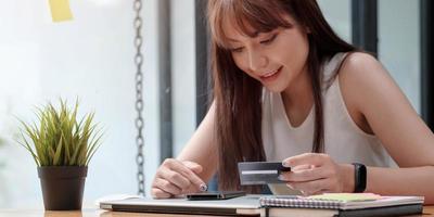 lachende vrouw gebruikt mobiele telefoon om online te winkelen met creditcard foto