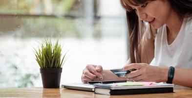 vrouw gebruikt mobiele telefoon om online te winkelen met creditcard foto