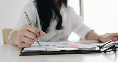 close-up van zakenvrouw investeringsadviseur analyse bedrijf jaarlijks financieel verslag balansoverzicht werken met documenten grafieken. concept foto van economie, marketing