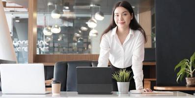 zelfverzekerde zakenvrouw die aan haar bureau staat en naar de camera glimlacht. foto