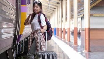 gelukkige vrouwelijke toerist op treinstation foto