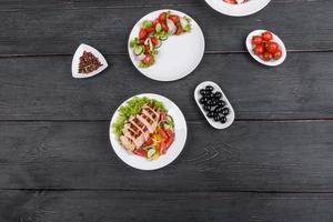 drie verse heerlijke salades met kip, tomaat, komkommer, uien en greens met olijfolie foto