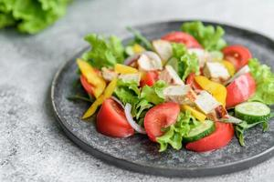 verse heerlijke salade met kip, tomaat, komkommer, uien en greens met olijfolie foto